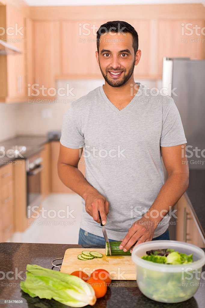 young indian man cooking stock photo