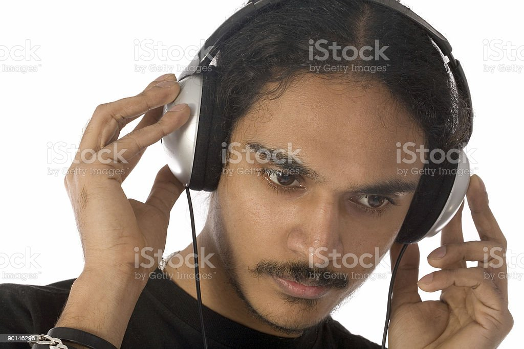 Young Indian man listens to music on headphones royalty-free stock photo