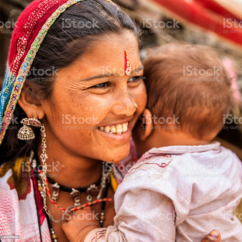 Young Indian mother holding her little baby, village near Jodhpur stock photo