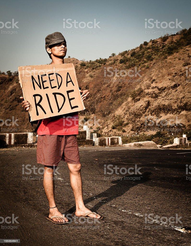 Young Indian Tourist Traveler man needs a ride hitch stock photo