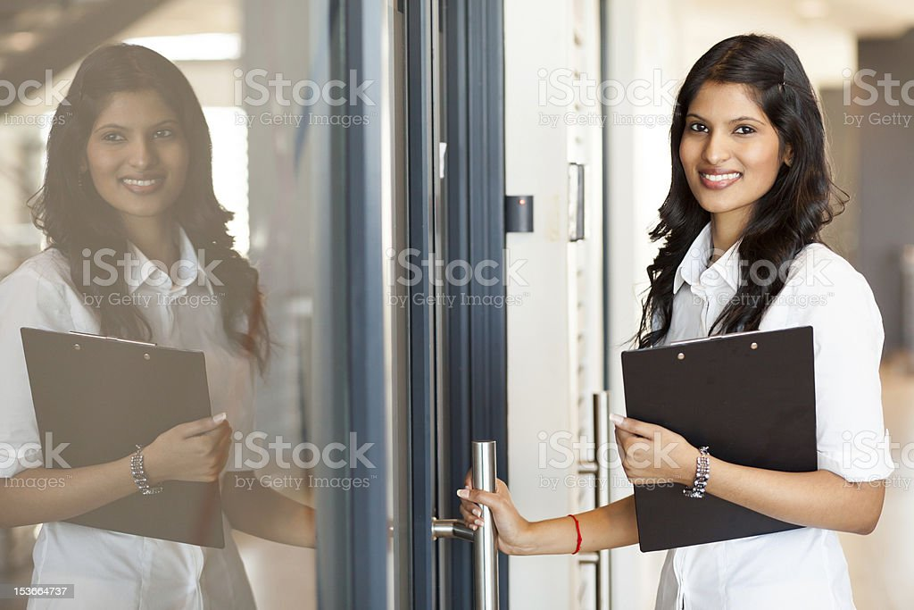 young indian white collar worker opening office door stock photo
