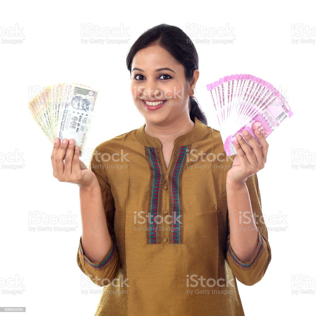 Young Indian woman holding currency notes agianst white background stock photo