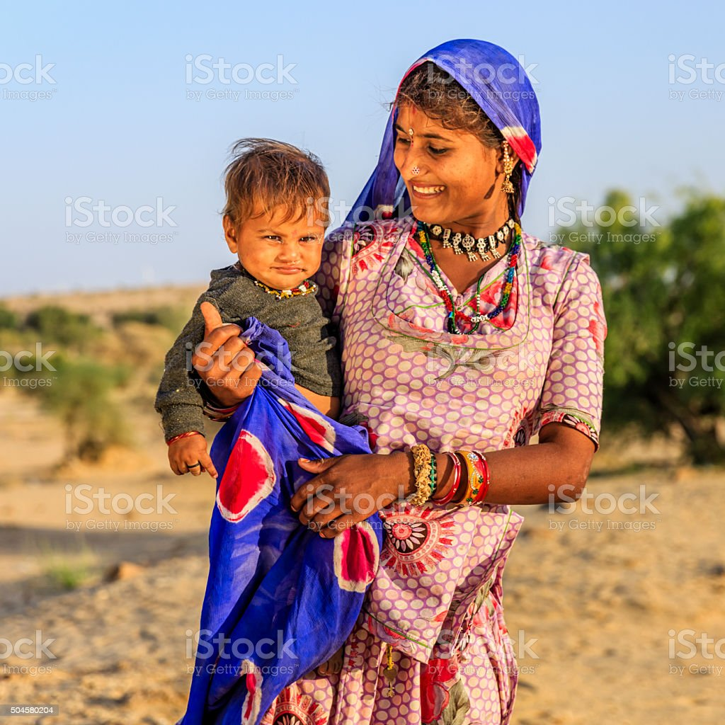 Young Indian woman holding her baby, desert village, India stock photo