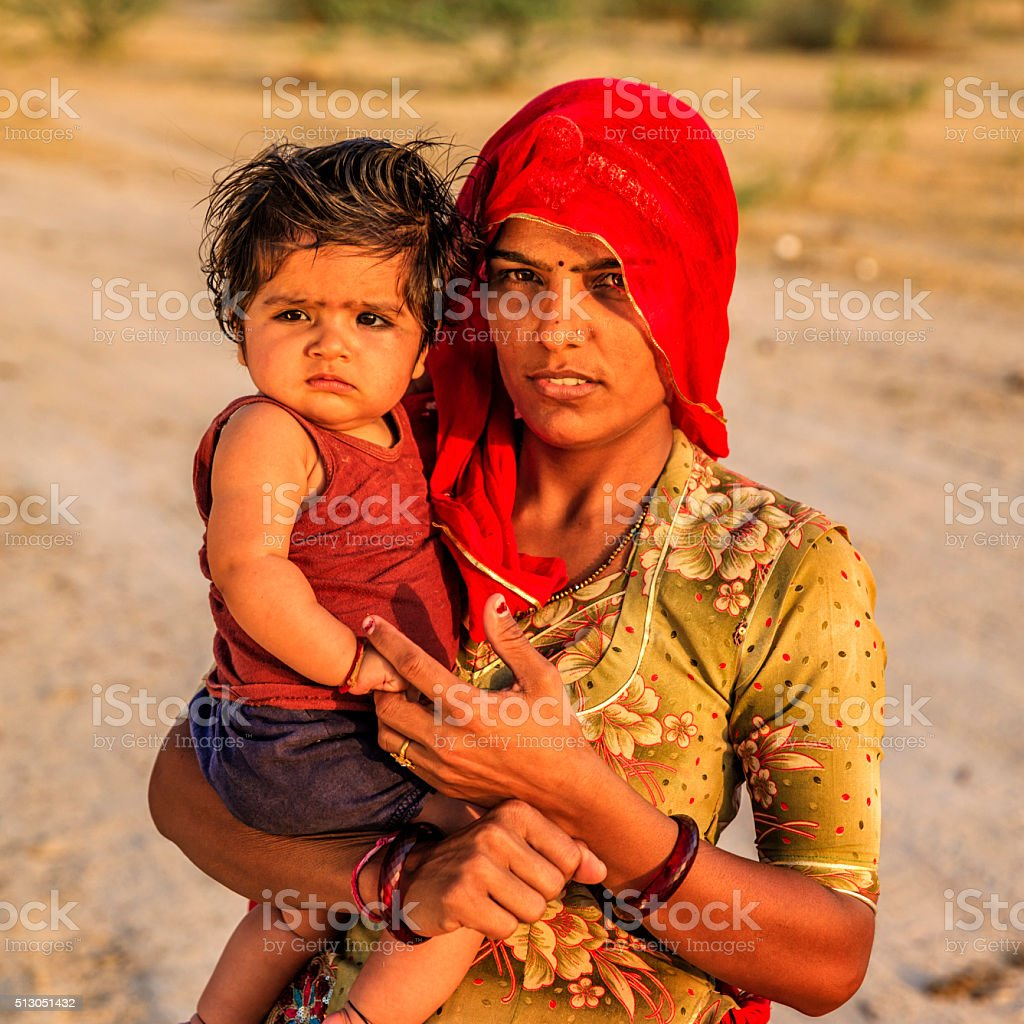 Young Indian woman holding her little baby, India stock photo