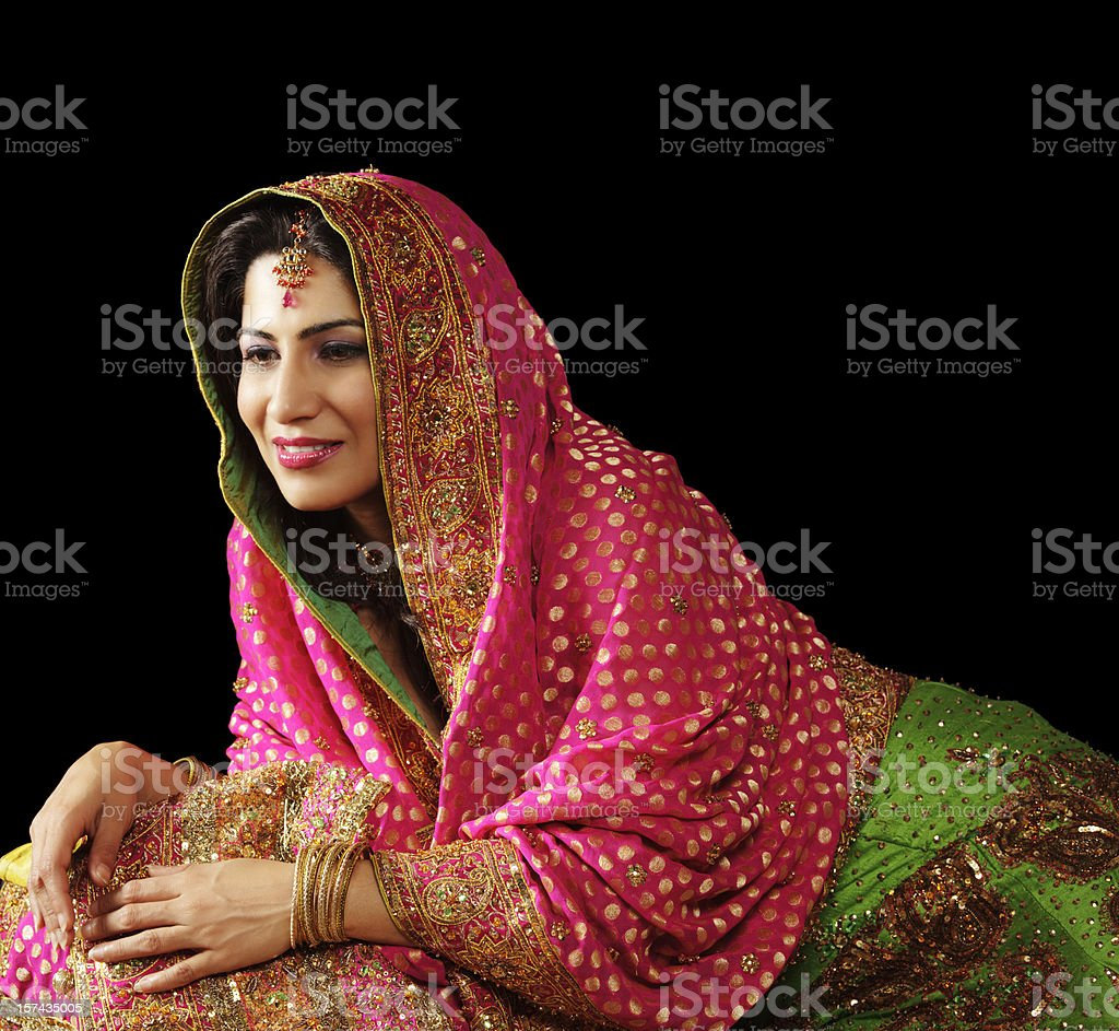 Young Indian woman in lehenga smiling contently (isolated on black) royalty-free stock photo