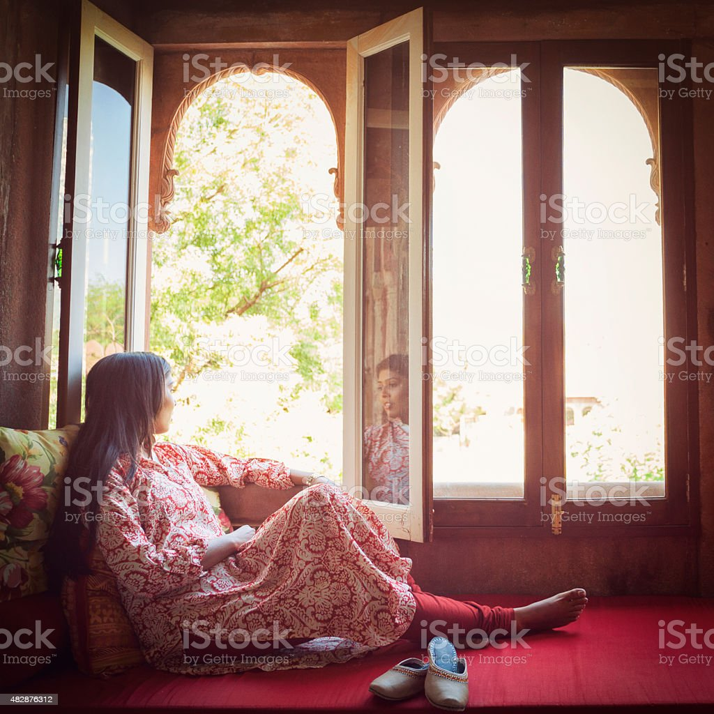 Young Indian Woman Looking out a Window stock photo
