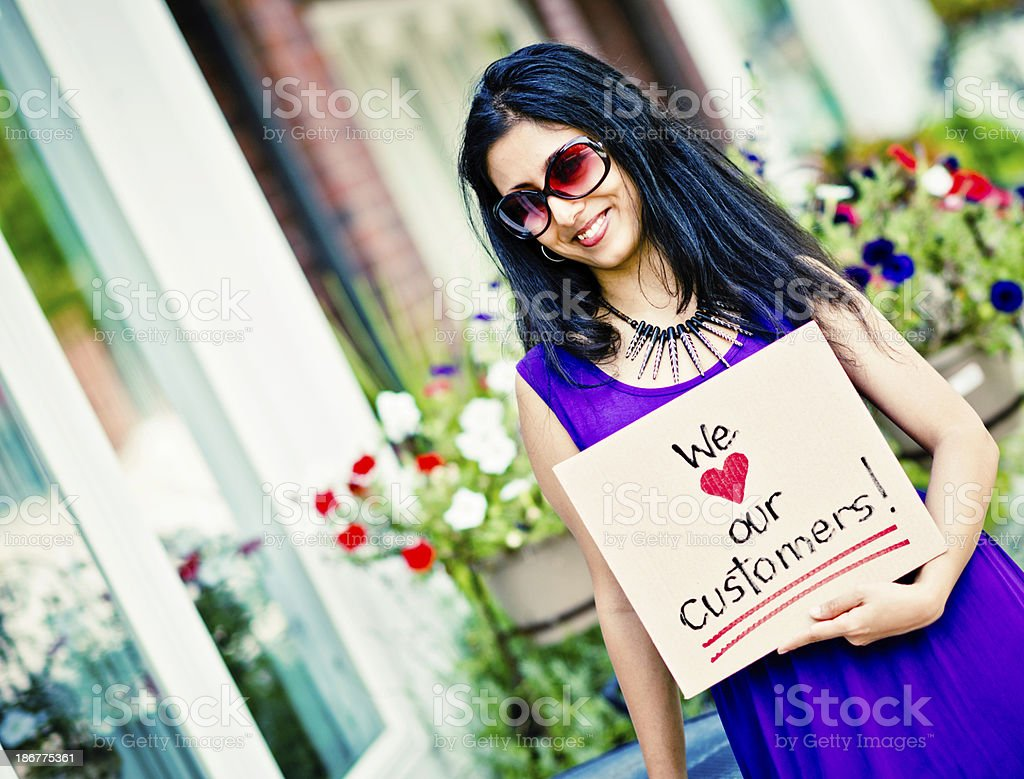 Young Indian Woman with Customer Appreciation Sign stock photo