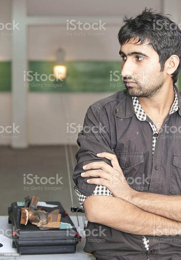 Young Indians with air pistol waiting at shooting gallery stock photo
