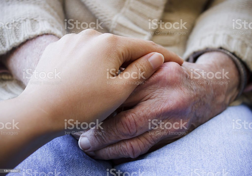A young individual holds their grandparent's hands royalty-free stock photo