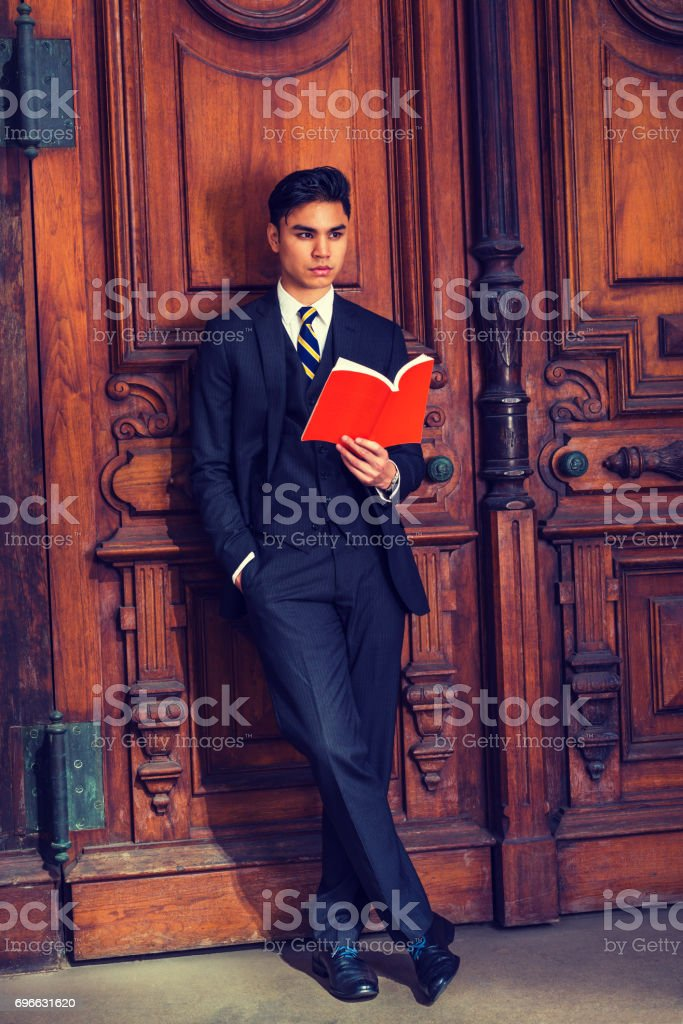 Young Indonesian American Man reading book in New York stock photo