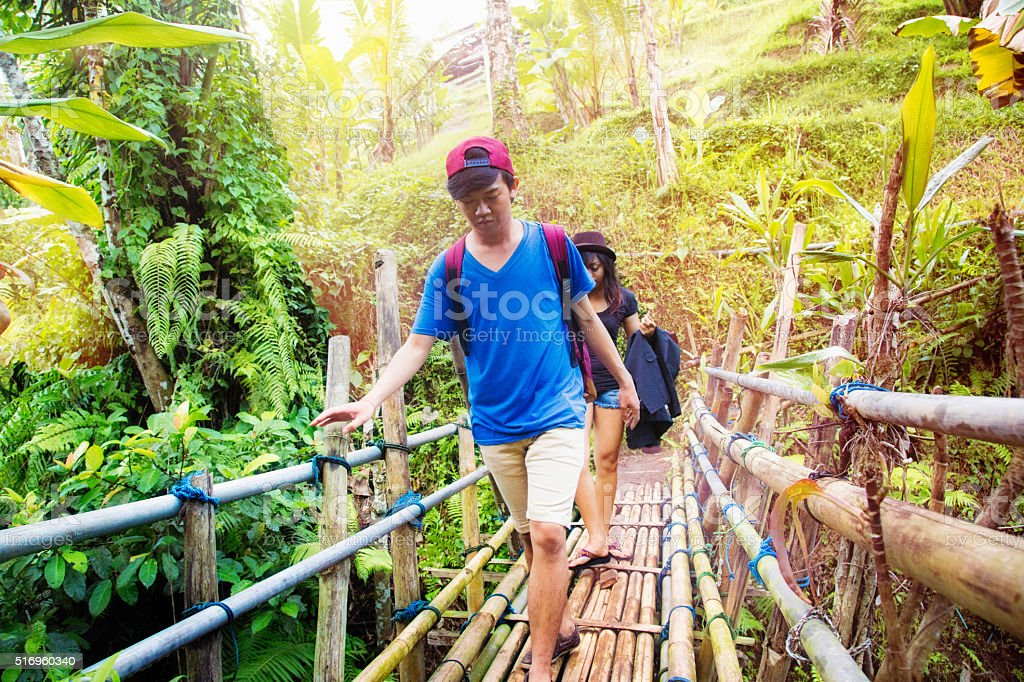 Young Indonesian couple crossing a bamboo bridge in jungle stock photo