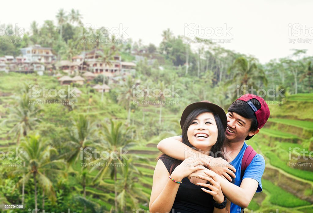 Young Indonesian couple having fun visiting Bali rice paddy wide stock photo