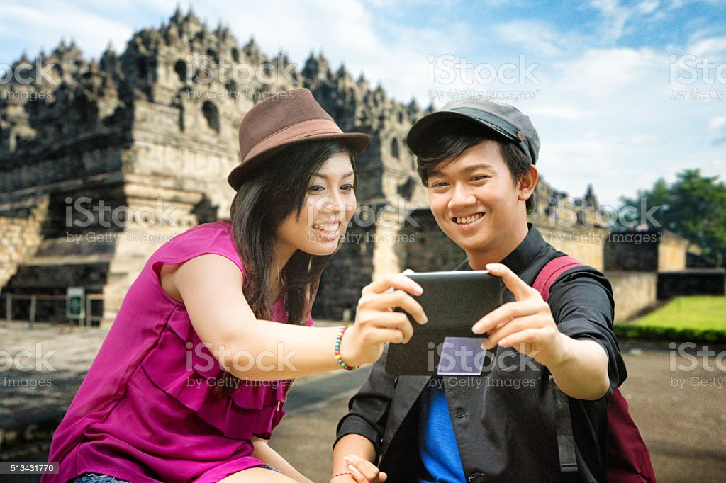 Young Indonesian couple shots selfie in front of Borobudur stock photo