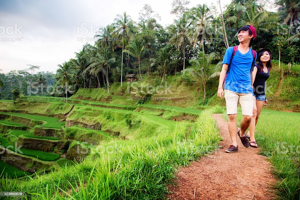 Young Indonesian couple visiting Bali terraced rice paddy stock photo