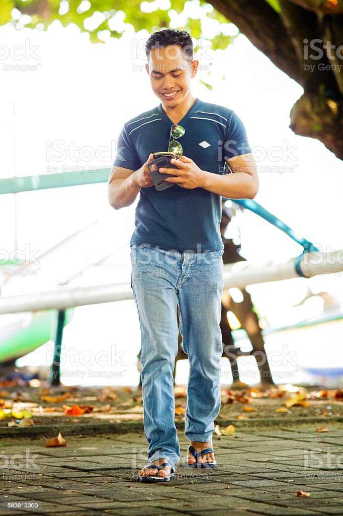 Young Indonesian male  playing mobile AR game Full length stock photo