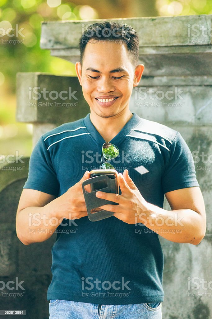 Young Indonesian male  playing mobile AR game in cemetery stock photo