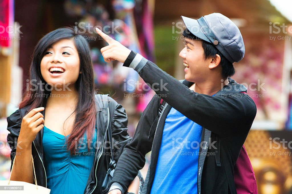 Young Indonesian man points something to his friend stock photo