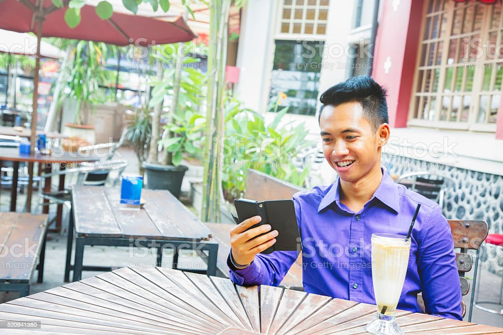 Young Indonesian man smiling at phone at outdoors cafe stock photo