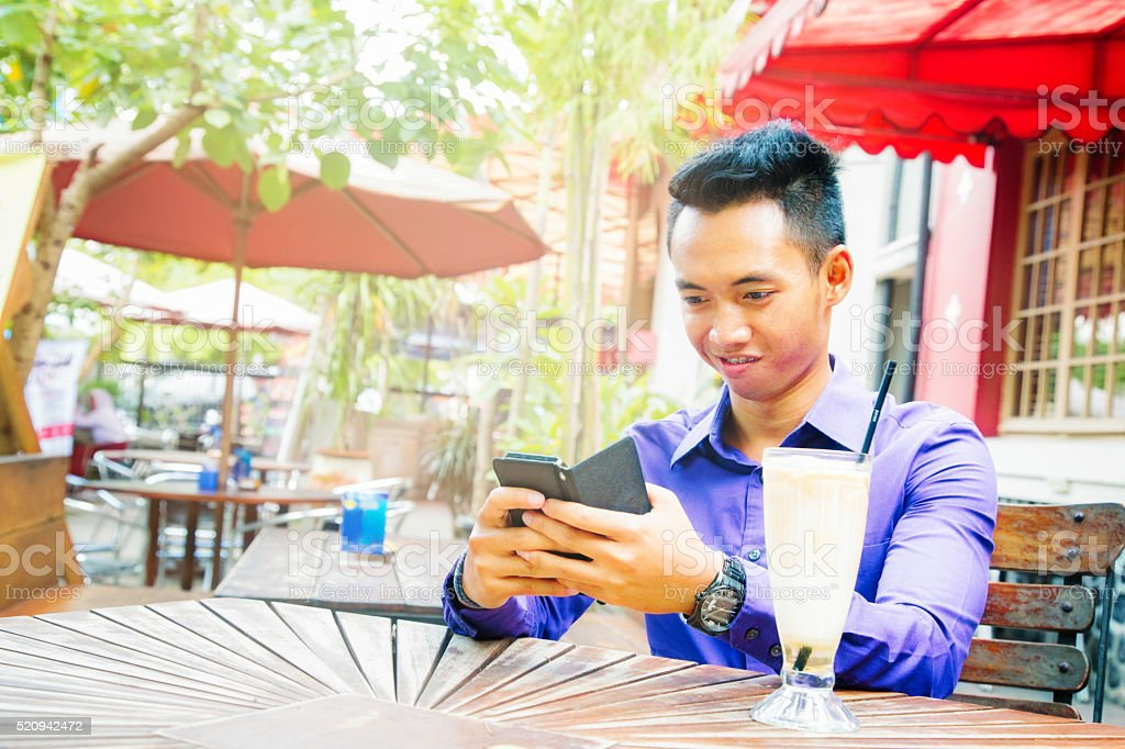 Young Indonesian man text messaging at cafe stock photo