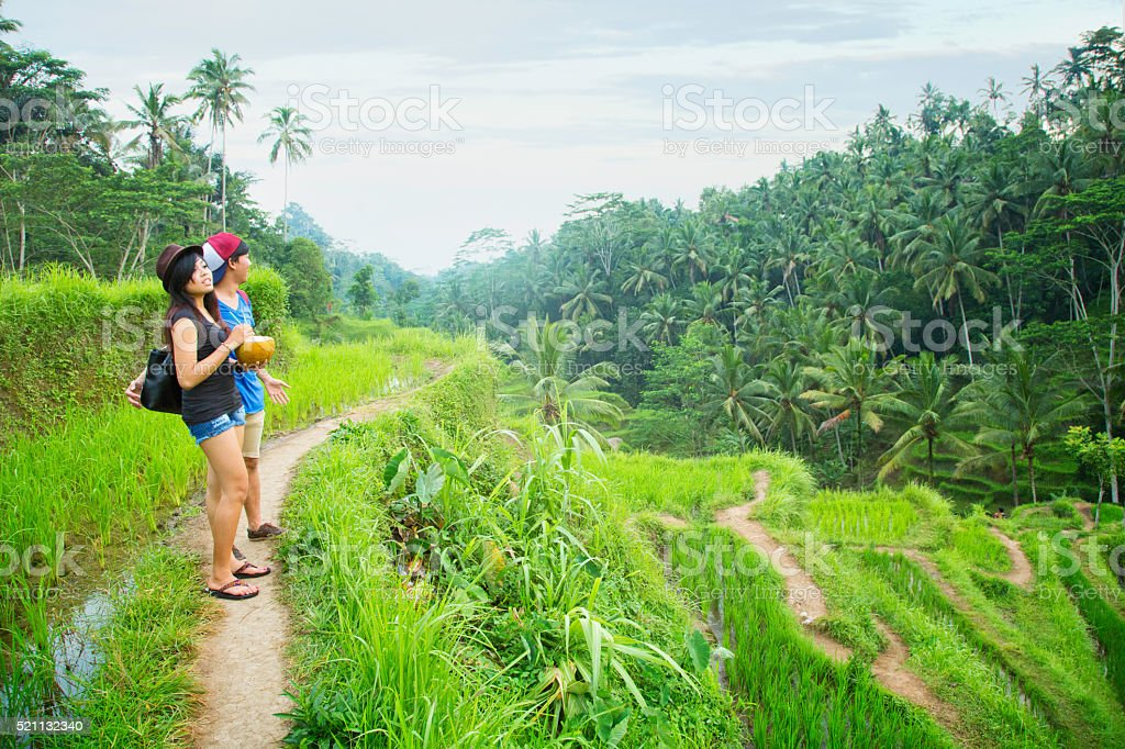 Young Indonesian tourists enjoying view at Bali terraced rice paddy stock photo