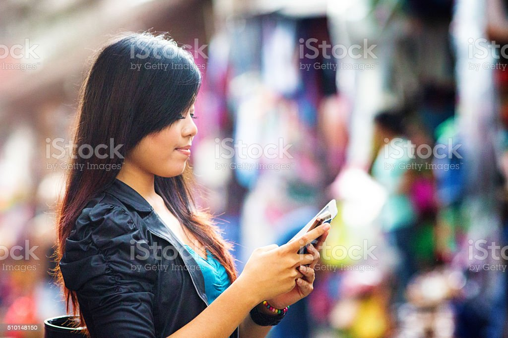 Young Indonesian woman text messaging profile at street market stock photo