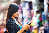 Young Indonesian woman text messaging profile at street market