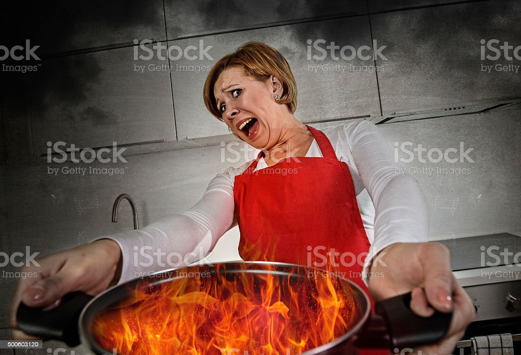 young inexperienced home cook woman in panic holding pot burning stock photo