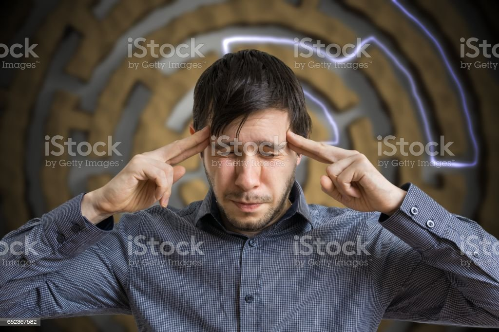 Young intelligent man is thinking and solving difficult task. stock photo