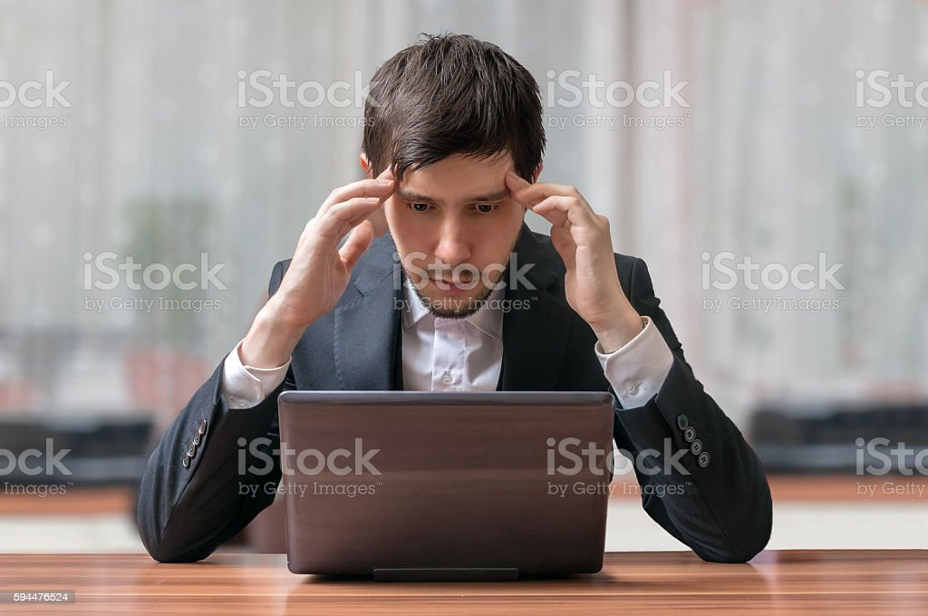 Young intend and thinking businessman working with laptop. stock photo