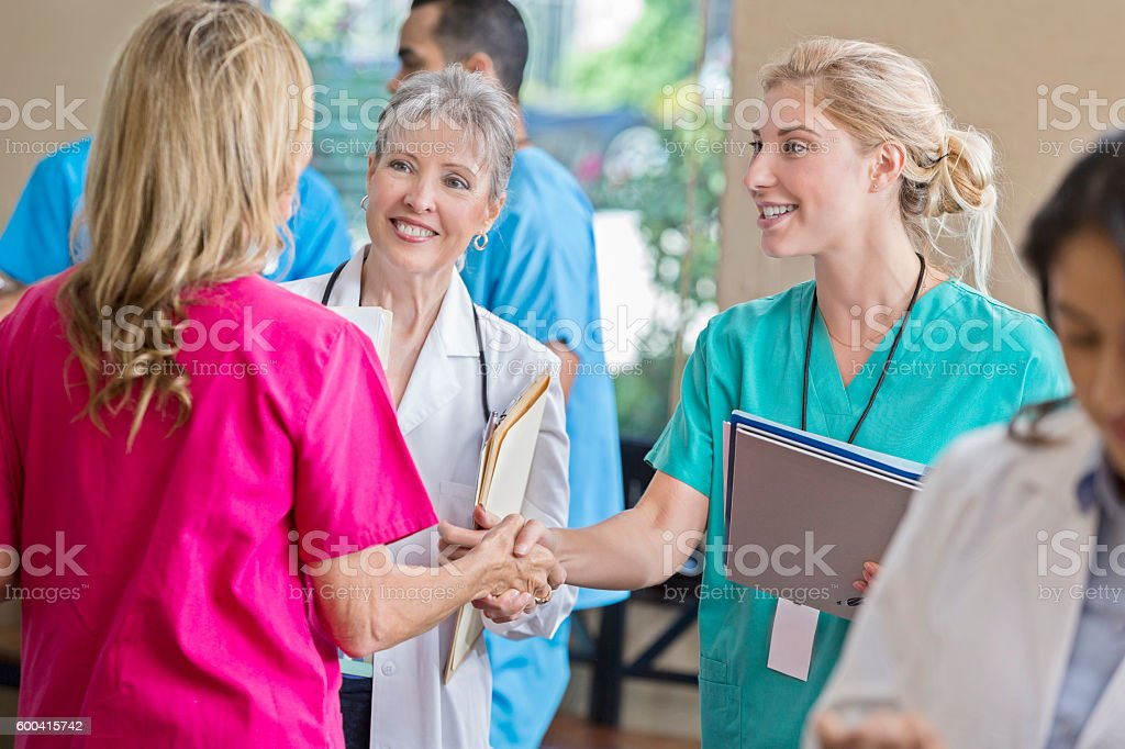 Young intern greets nurse during staff meeting stock photo