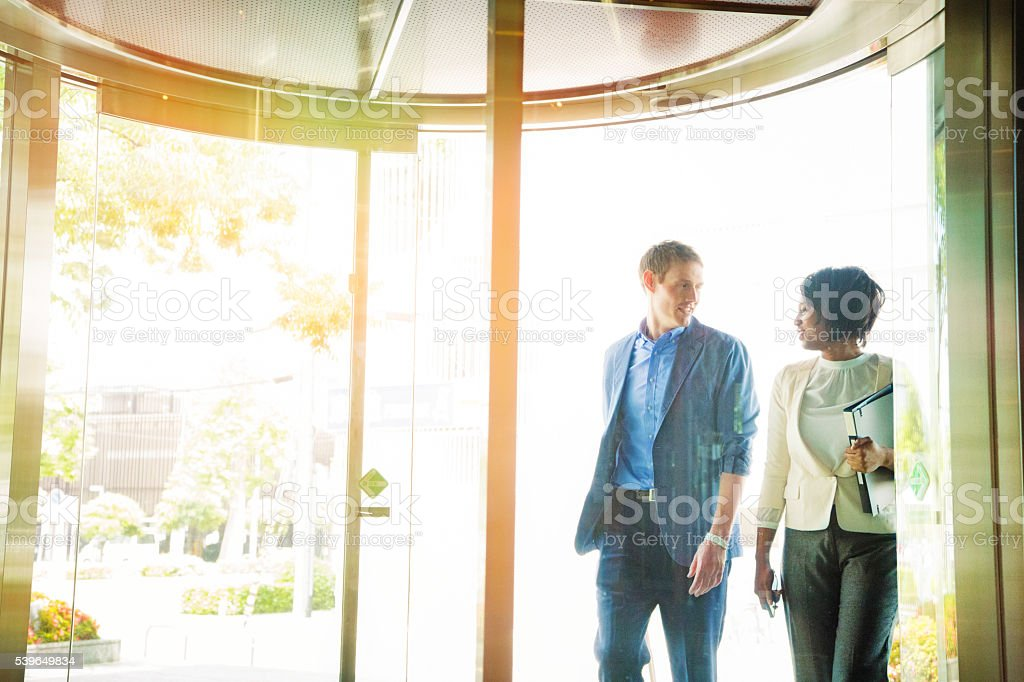 Young international team entering office lobby early morning chatting stock photo