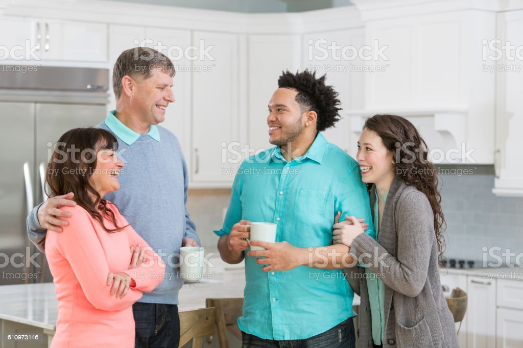 Young interracial couple in kitchen with senior parents stock photo