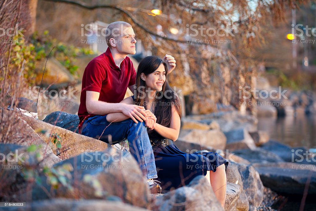 Young interracial couple sitting together on rocky shoreline by lake stock photo