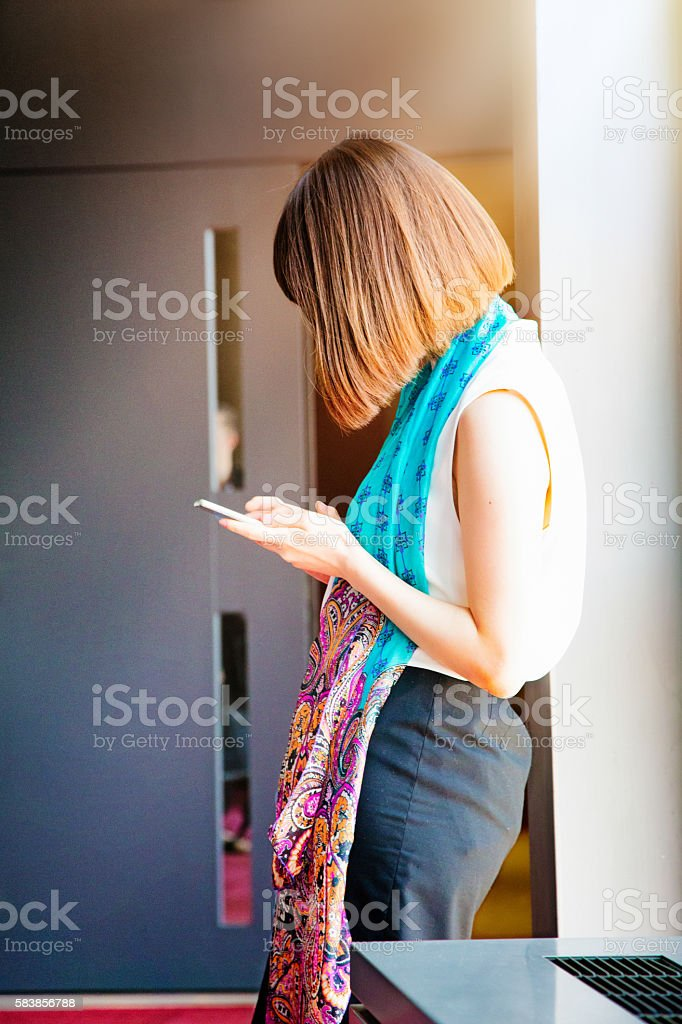 Young introvert Japanese female using her mobile phone stock photo