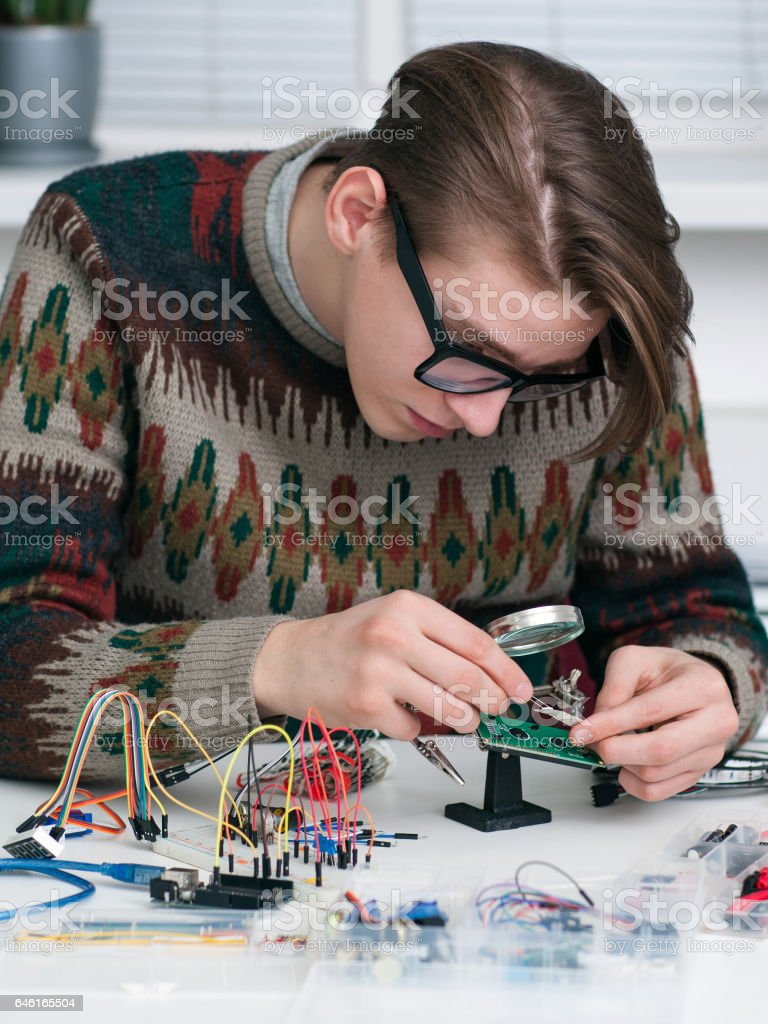 Young inventor examing electronic component stock photo