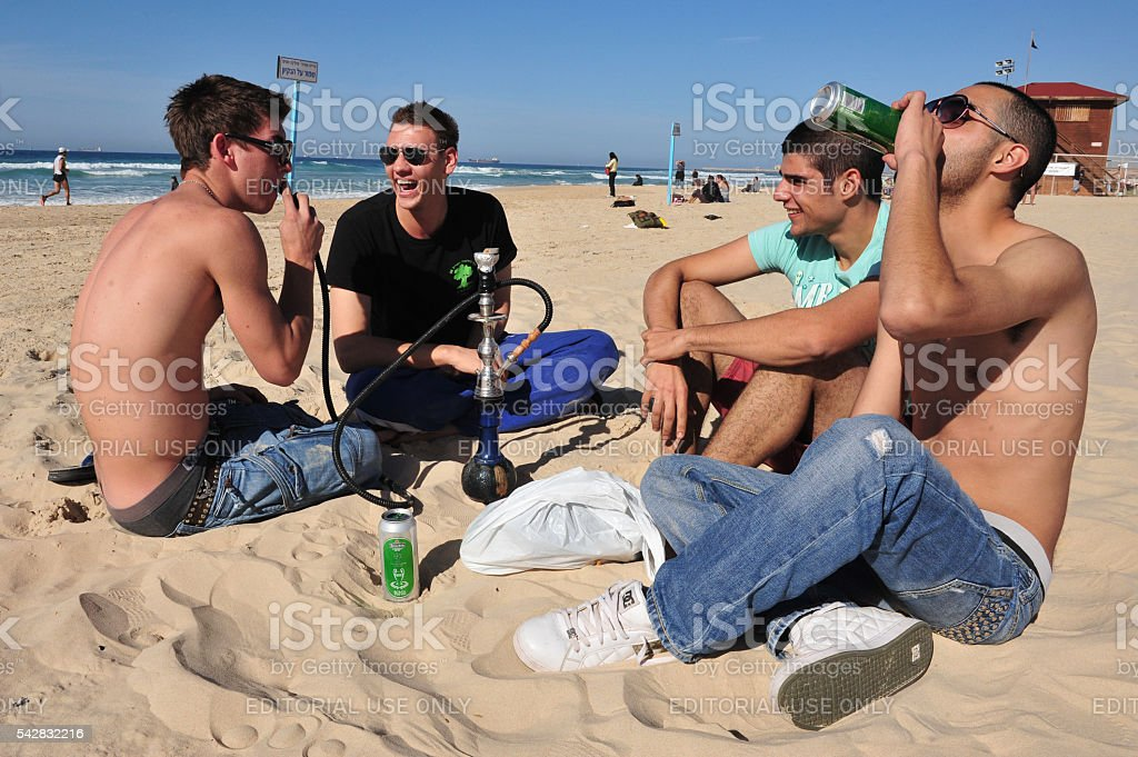 Young Israeli men smoke and drink alcohol on the beach stock photo