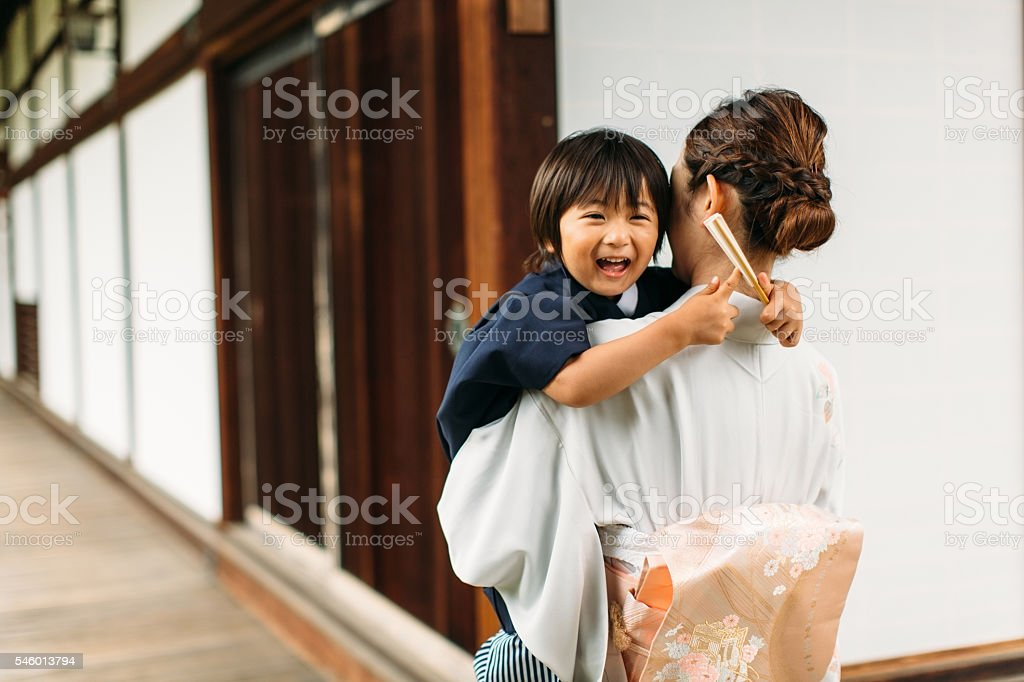 Young Japanese Boy is Laughing in Mother's Arms stock photo