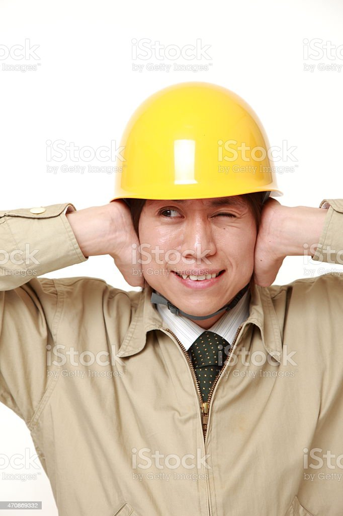 Young Japanese construction worker suffers from noise stock photo