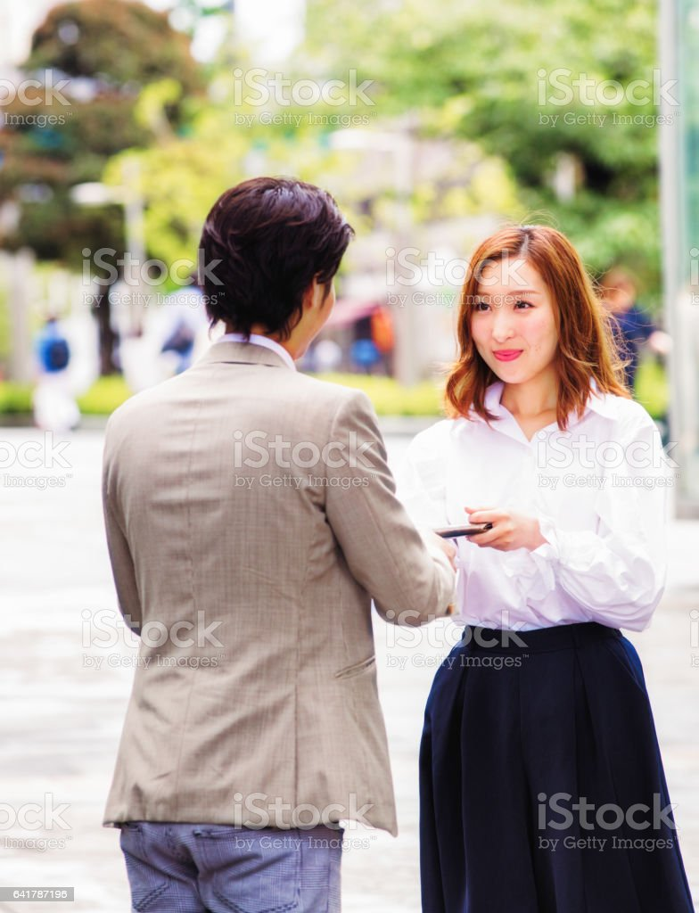 Young Japanese female worker hands her card to colleague bowing stock photo