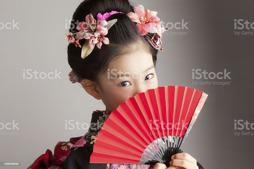 Young Japanese girl celebrating Shichi-Go-San with a red fan stock photo