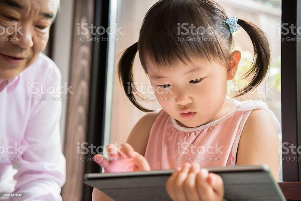 Young Japanese girl concentrating on digital tablet stock photo