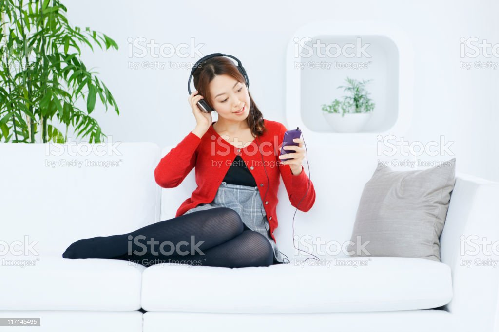 Young Japanese Girl Listening to Music, Holding Headphone and Device royalty-free stock photo