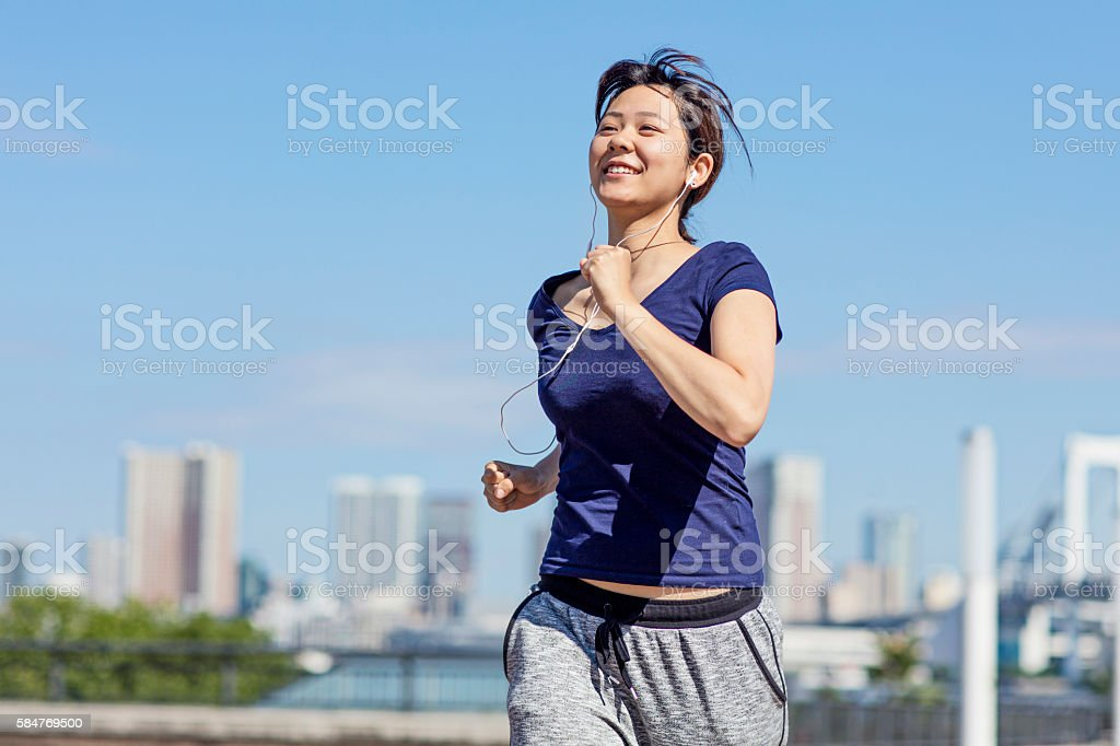 Young Japanese girl running in the morning at Tokyo stock photo
