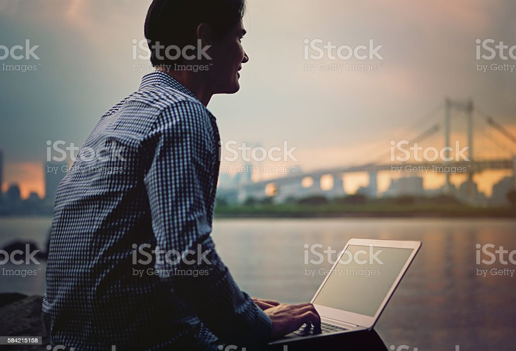 Young Japanese man is working at the front Rainbow bridge. stock photo