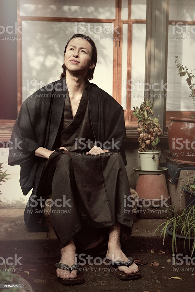 Young japanese man sitting in the garden of his house stock photo
