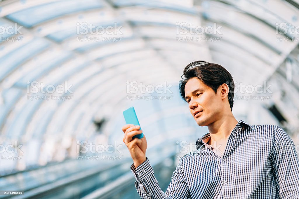 Young japanese man texting on the phone stock photo