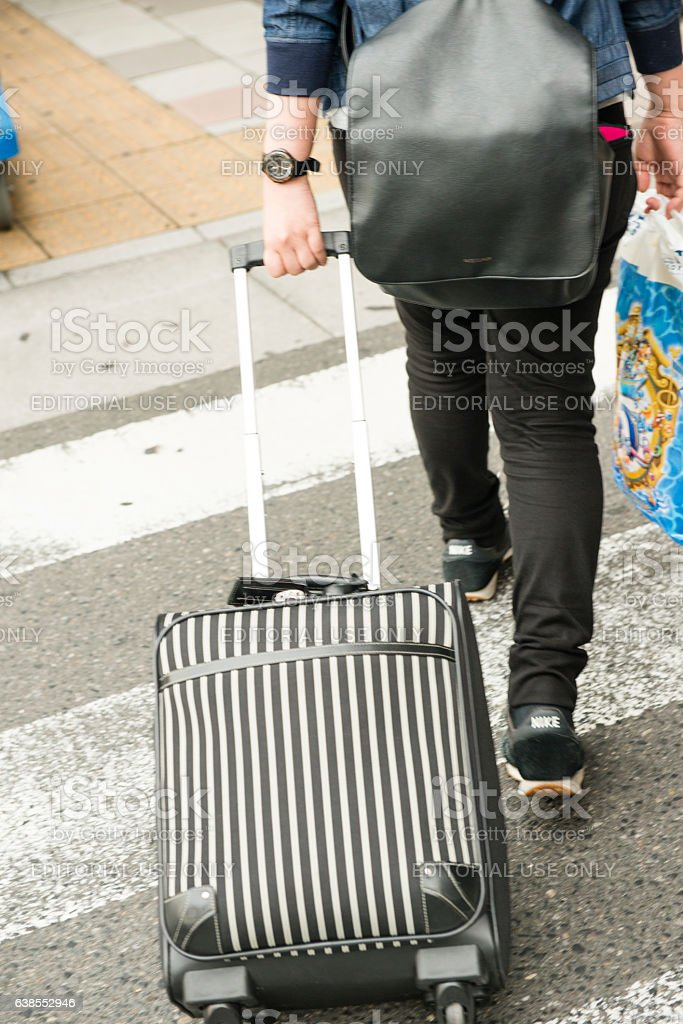 Young Japanese Man Traveling with Rolling Suitcase Nagoya Station Japan stock photo