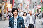 Young Japanese man walking down Tokyo Street