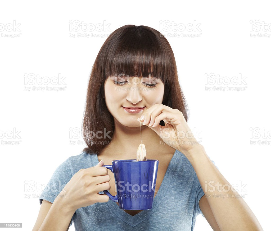 Young Japanese woman dipping tea bag into cup royalty-free stock photo