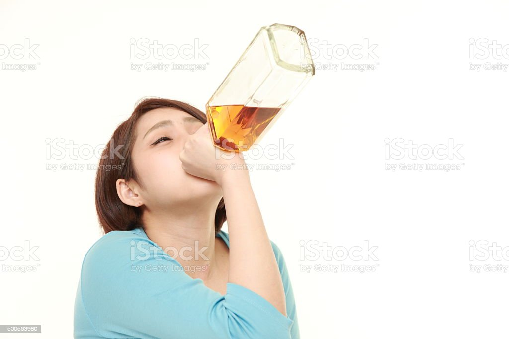 young Japanese woman drinking straight from a bottle stock photo